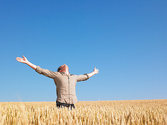 Man in Wheat Field With Arms Outstretched